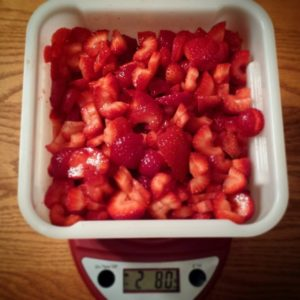 Strawberries have been hulled, chopped, and weighed.